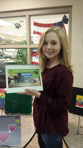 Amber Simberly (11) poses with her children's book for Spanish.